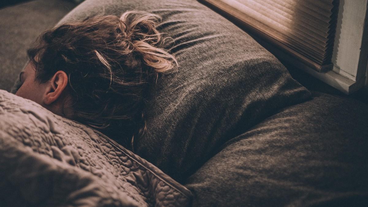 Žena leží v posteli a trápí ji nespavost.