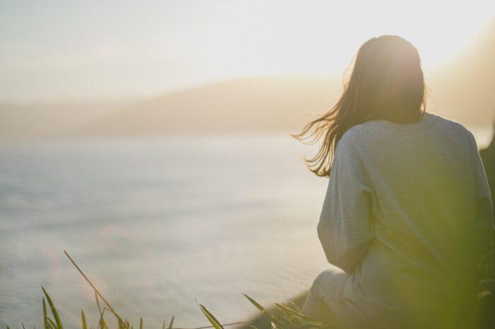 Dívka sedí na sluníčku a může chytit úpal a úžeh.