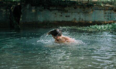 Mladík se věnuje otužování ve studené vodě.